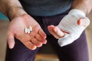 man holding three white medication pills