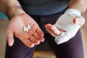 man holding three white medication pills
